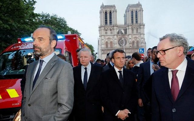 French Prime Minister Edouard Philippe (L), and French President Emmanuel Macron (3rd L) gather near the entrance of the Notre Dame de Paris Cathedral in Paris, as flames engulf its roof on April 15, 2019. (PHILIPPE WOJAZER/POOL/AFP)