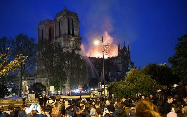 Crowds look on as flames and smoke billow from the roof at Notre-Dame Cathedral in Paris on April 15, 2019. (ERIC FEFERBERG / AFP)