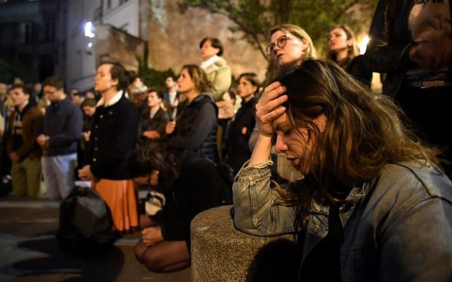 People kneel on the pavement as they pray outside the Notre Dame Cathedral in Paris on April 15, 2019, after the medieval church is decimated by a fire. (Eric Feferberg/AFP)