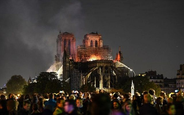 Bystanders look on as flames and smoke are seen billowing from the roof at Notre-Dame Cathedral in Paris on April 15, 2019. (ERIC FEFERBERG / AFP)