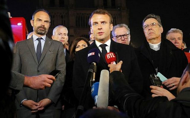 French President Emmanuel Macron (C) is accompanied by Mayor of Paris Anne Hidalgo (3L), French Prime Minister Edouard Philippe (L) French Culture Minister Franck Riester (2L) and Archbishop of Paris Michel Aupetit as he speaks at Notre-Dame Cathedral in Paris on April 15, 2019, after a fire engulfed the building. (PHILIPPE WOJAZER / POOL / AFP)