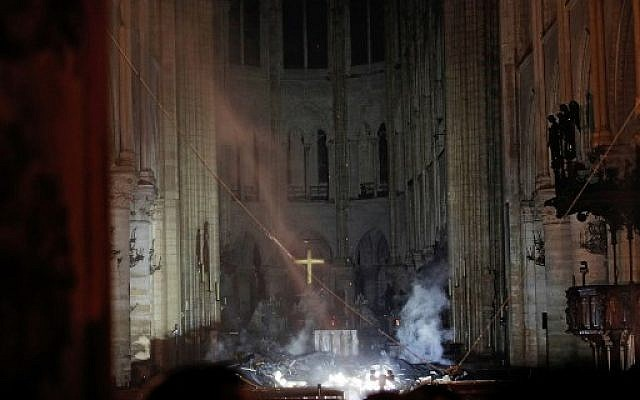 Smoke rises in front of the altar cross at Notre Dame Cathedral in Paris on April 15, 2019, after a fire engulfed the building. (PHILIPPE WOJAZER / POOL / AFP)