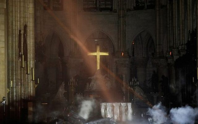Smoke rises around the alter in front of the cross inside the Notre-Dame Cathedral as the fire continued to burn on April 16, 2019 in Paris. (Photo by PHILIPPE WOJAZER / POOL / AFP)