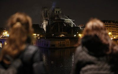 Bystanders look on as flames and smoke billow from the roof at Notre-Dame Cathedral in Paris early on April 16, 2019. (Zakaria ABDELKAFI / AFP)