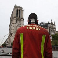 A firefighter stands outside Notre Dame Cathedral in Paris on April 16, 2019, in the aftermath of a fire that caused its spire to crash to the ground. (Zakaria ABDELKAFI / AFP)