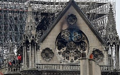 Inspectors are seen on the roof of the landmark Notre Dame Cathedral in central Paris on April 16, 2019, the day after a fire ripped through its main roof. (Photo by Lionel BONAVENTURE / AFP)