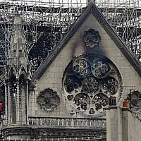 Inspectors are seen on the roof of the landmark Notre-Dame Cathedral in central Paris on April 16, 2019, the day after a fire ripped through its main roof. (Lionel BONAVENTURE / AFP)