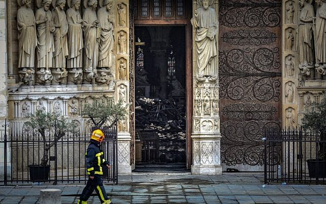 A firefighter walks along Notre-Dame-de Paris on April 16, 2019 in Paris in the aftermath of a fire that devastated the cathedral. ( LUDOVIC MARIN / POOL / AFP)