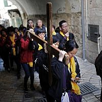 Chinese Catholic pilgrims carry a wooden cross along the Via Dolorosa in Jerusalem's Old City during the Good Friday procession on April 19, 2019. (Thomas Coex/AFP)