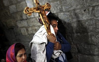 A Catholic pilgrim carries a wooden cross along the Via Dolorosa in Jerusalem's Old City during the Good Friday procession on April 19, 2019. (Thomas Coex/AFP)