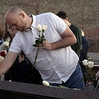 Will Beck, a Columbine High School massacre survivor, places flowers at the Columbine Memorial at Clement Park in Littleton, Colorado, during a community vigil for the 20th anniversary of the Columbine High School mass shooting on April 19, 2019. (Jason Connolly / AFP)