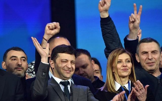 Ukrainian comedian and presidential candidate Volodymyr Zelensky (C) and his wife Olena together with members of his crew react during a presidential election debate with Ukraine's current President at The Olympic Stadium in Kiev on April 19, 2019. (Sergei SUPINSKY / AFP)