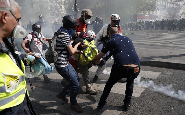 An injured woman is evacuated to receive medical assistance during an anti-government demonstration called by the 'Yellow Vests' (gilets jaunes) movement for the 23rd consecutive Saturday, on April 20, 2019 in Paris. (Zakaria ABDELKAFI / AFP)