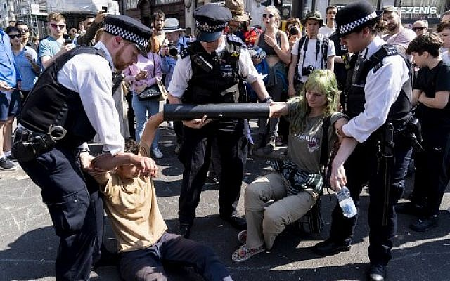 Police officers move climate change activists with their hands glued to a pipe as they continue to block the road at Oxford Circus in London on April 20, 2019. (Niklas HALLE'N / AFP)