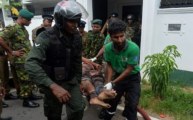An injured Sri Lankan Special Task Force (STF) member is carried by colleagues after a blast in a house, which was detonated as security forces searched the property, in the Orugodawatta area of the capital Colombo on April 21, 2019.(ISHARA S. KODIKARA / AFP)