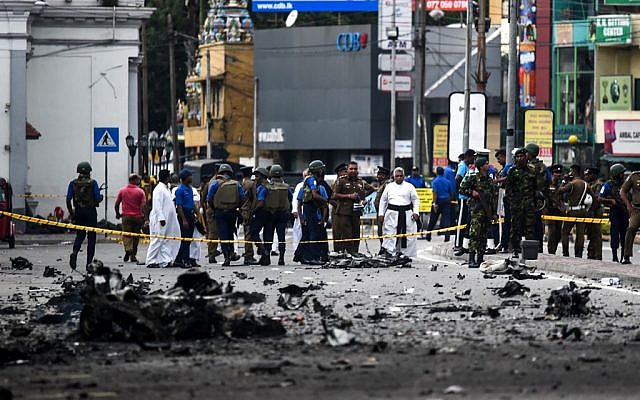 Sri Lankan security personnel inspect the debris of a car after it explodes when police tried to defuse a bomb near St. Anthony's Shrine as priests look on in Colombo on April 22, 2019, a day after the series of bomb blasts targeting churches and luxury hotels in Sri Lanka. (Jewel SAMAD / AFP)