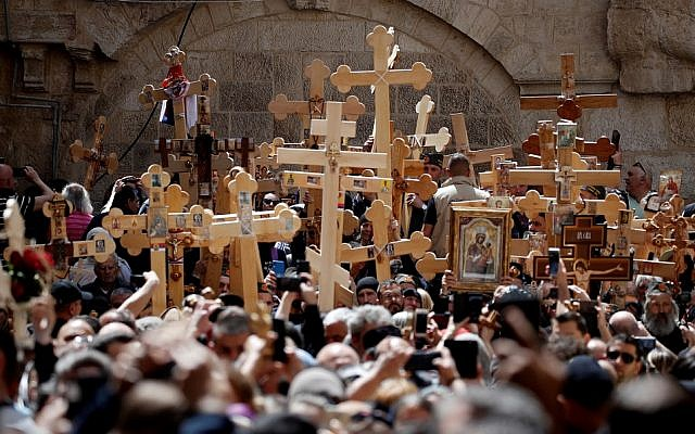 Orthodox Christians gather with wooden Crosses in front of the Church of the Holy Sepulchre as they celebrate the Good Friday in a procession on Via Dolorosa in the Old City of Jerusalem, on April 26, 2019. (Thomas Coex/AFP)