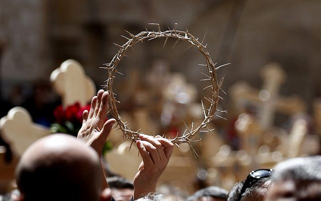 Orthodox Christians brandish the crown of thorns in the Church of the Holy Sepulchre after they celebrated the Good Friday in a procession on Via Dolorosa in the Old City of Jerusalem, on April 26, 2019. (THOMAS COEX / AFP)