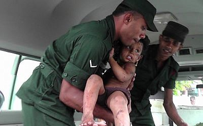 Soldiers evacuate an injured child after they raid what believed to be an Islamist safe house in the eastern town of Kalmunai on April 27, 2019 (STRINGER / AFP)