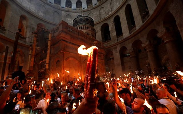 Christian Orthodox worshippers hold up candles lit from the'Holy Fire' as they gather in the Church of the Holy Sepulchre in Jerusalem's Old City on April 27, 2019 during the Orthodox Easter. (GALI TIBBON / AFP)