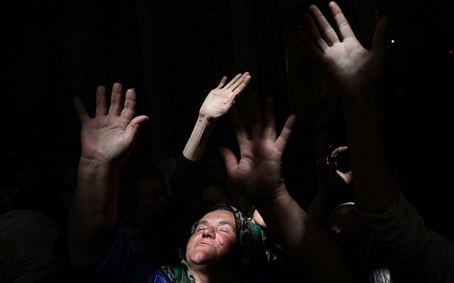 Christian Orthodox worshippers raise their hands as a beam of light from the 'Holy Fire penetrates in the Church of the Holy Sepulchre in Jerusalem's Old City on April 27, 2019 during the Orthodox Easter. (GALI TIBBON / AFP)