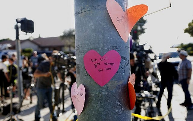 Hand-written notes are displayed on a light post across the street from the Chabad of Poway Synagogue after a shooting on April 27, 2019 in Poway, California. (SANDY HUFFAKER / AFP)