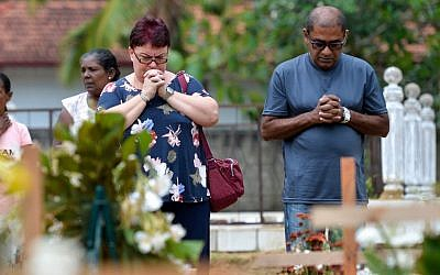 Relatives pay their respects in front of the graves of the victims of recent bomb blasts at St. Sebastian's Church in Negombo, Sri Lanka, on April 28, 2019, a week after a series of jihadist bomb blasts targeted churches and luxury hotels on Easter Sunday. (Ishara S. Kodikara/AFP)