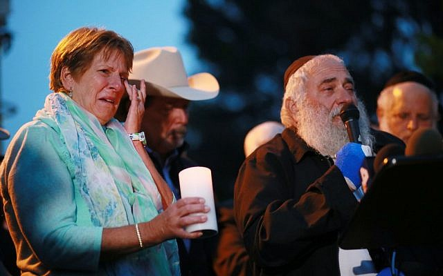 Corrie Vaus (L) wipes a tear, next to her husband, Poway Mayor Steve Vaus (2nd L), while listening to Rabbi Yisroel Goldstein describe the shooting during a candlelight vigil for the victim of the Chabad of Poway Synagogue shooting on April 28, 2019 in Poway, California (SANDY HUFFAKER / AFP)
