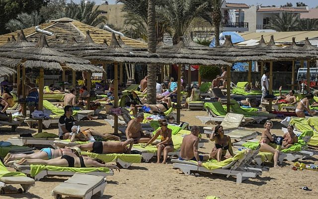 In this file photo taken on April 3, 2019, tourists sunbathe on a beach in Egypt's Red Sea resort town of Hurghada. (Photo by Mohamed el-Shahed / AFP)