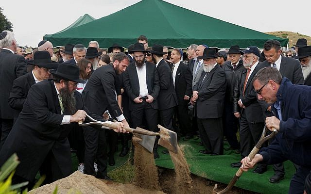"""Members of the Jewish community and other mourners shovel dirt over the coffin during the burial service for Lori Gilbert Kaye, who was killed in the Chabad of Poway Synagogue shooting, at El Camino cemetery in San Diego, California, on April 29, 2019. - A rabbi who carried on preaching despite being wounded in the latest deadly shooting at a US synagogue said on April 28 that Jews would not be intimidated by the """"senseless hate"""" of anti-semitism. (Photo by Sandy HUffaker / AFP)"""