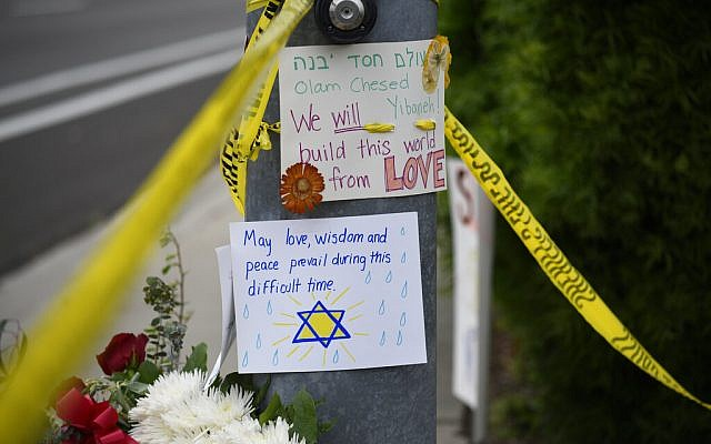 Flowers and signs sit at a memorial across the street from the Chabad of Poway synagogue, on Sunday, April 28, 2019, in Poway, California. A man opened fire Saturday inside the synagogue near San Diego, as worshipers celebrated the last day of a major Jewish holiday. (AP Photo/Denis Poroy)