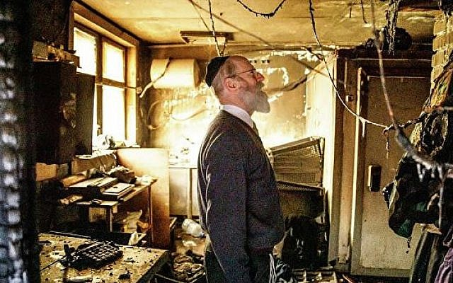 A person inspects the damage from a fire set at the Torat Chaim Yeshiva on the eve of Passover (Courtesy/Torat Chaim Yeshiva)