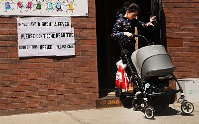 A sign warns of measles in the Orthodox Jewish community of Williamsburg, Brooklyn, in New York City, April 10, 2019. (Spencer Platt/Getty Images/via JTA)
