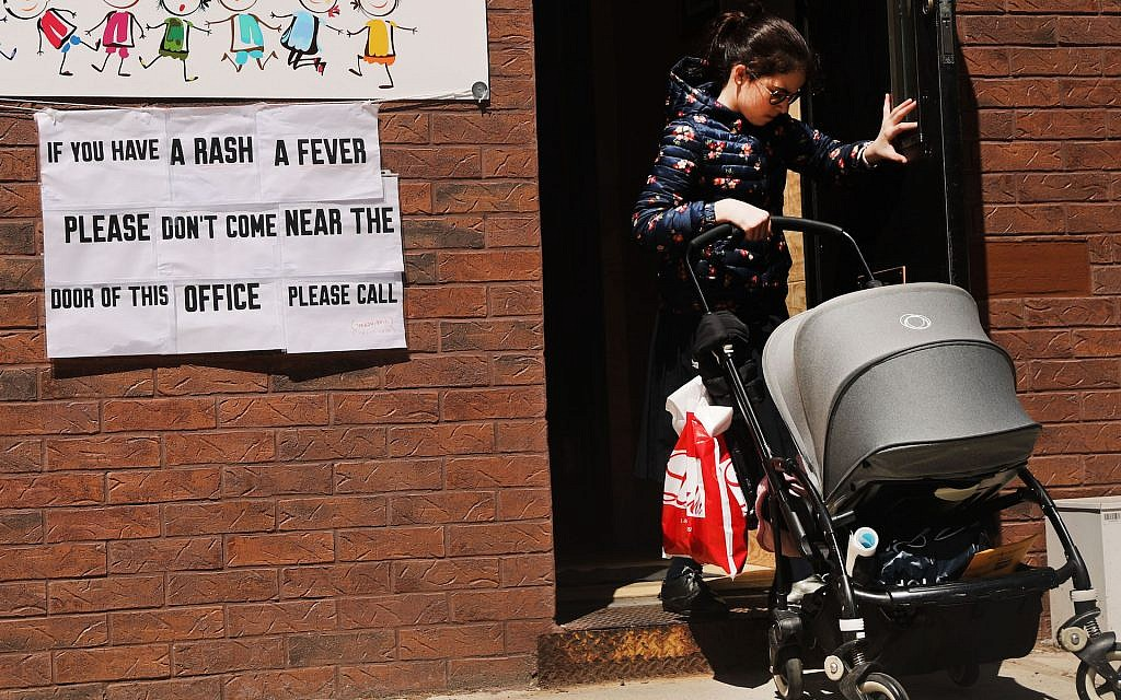A sign warns of measles in the Orthodox Jewish community of Williamsburg, Brooklyn, in New York City, April 10, 2019. (Spencer Platt/Getty Images via JTA)