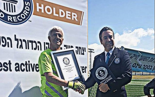 Isaak Hayik (left) presented with the  Guinness World Record for the oldest living active pro soccer player by an unidentified Guinness official, April 5, 2019 (Facebook)
