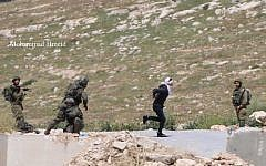 An IDF solider chases a Palestinians suspect as he tries to escape in the West Bank town of Tuqu on April 18, 2019. (Mohammad Hmeid)