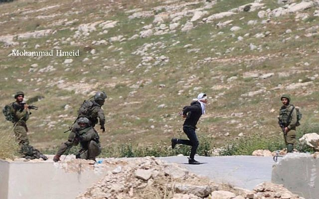 An IDF soldier chases a Palestinians suspect as he tries to escape in the West Bank town of Tuqu on April 18, 2019. (Mohammad Hmeid)