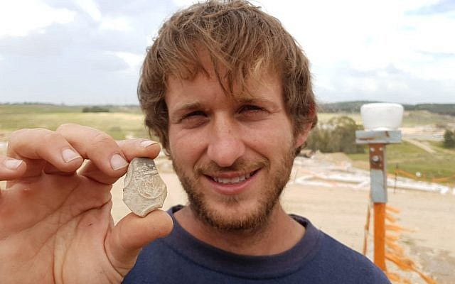 IAA Archaeologist Avinoam Lehavi holding the 2000-year-old oil lamp sherd decorated with a menorah from the excavation near Tel Beersheba. (Anat Rasiuk, Israel Antiquities Authority)