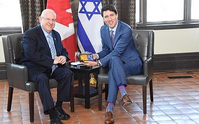 Israel's President Reuven Rivlin (left) presents Canadian Prime Minister Justin Trudeau with a pair of made-in-Israel socks, April 1, 2019. (Mark Neiman,GPO)