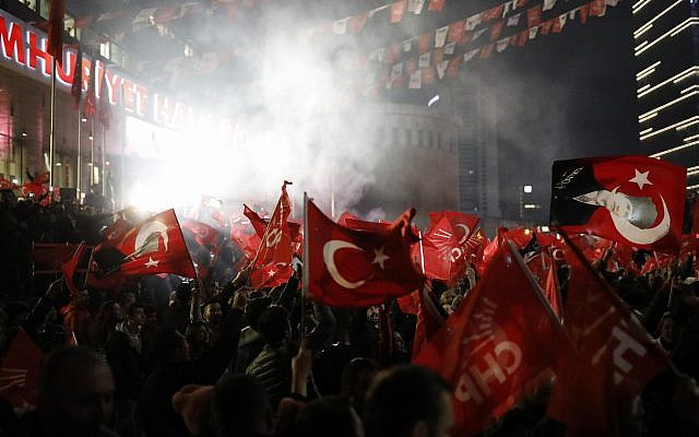 Supporters of the Republican People's Party, CHP, wave Turkish flags, and one with a portrait of Kemal Ataturk, right, as they celebrate after preliminary results of the local elections were announced in Ankara, Turkey, April 1, 2019. (Burhan Ozbilici/AP)