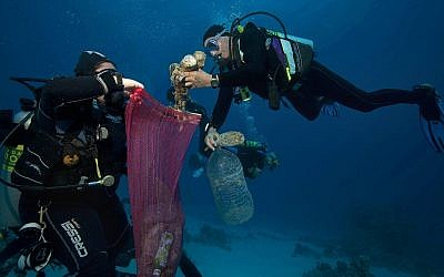 In this June 8, 2018 photo, divers collect plastic and other debris during a cleanup organized by Camel Dive Club, at a dive site off the coast of the Red Sea resort of Sharm el Sheikh, in southern Sinai, Egypt. (AP Photo/Thomas Hartwell)