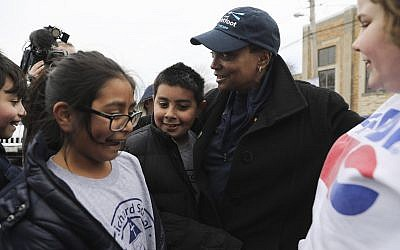 Grammar school students stop to say hello and hug mayoral candidate Lori Lightfoot outside a 14th Ward polling location, Tuesday, April 2, 2019, in Chicago. (Abel Uribe/Chicago Tribune via AP)
