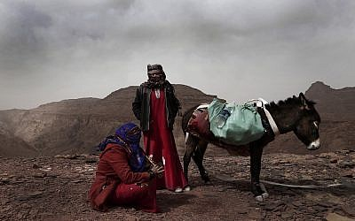 In this March 30, 2019 photo, Umm Yasser, the first Bedouin female guide from the Hamada tribe, looks at Umm Soliman as she plays the flute, near Wadi Sahw, Abu Zenima, in South Sinai, Egypt. (AP Photo/Nariman El-Mofty)