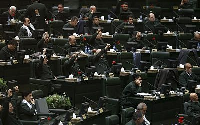 Wearing the uniform of the Islamic Revolutionary Guard Corps, Iranian lawmakers chant 'Death to America' and other slogans during an open session of parliament in Tehran, Iran, on April 9, 2019. (AP Photo/ Hamidreza Rahel/ICANA)