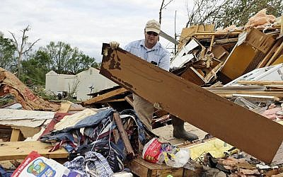 Roman Brown moves part of a wall out of his way as he looks for a friend's medicine in their destroyed home along Seely Drive outside of Hamilton, Mississippi, after a storm moved through the area on April 14, 2019. (AP Photo/Jim Lytle)