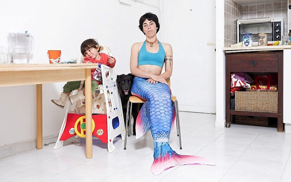 In this Tuesday, Feb. 26, 2019 photo, Ommer Globerman, a member of the Israeli Mermaid Community, poses for a portrait as she wears a mermaid tail at her home in Ashkelon, Israel. (AP Photo/Oded Balilty)
