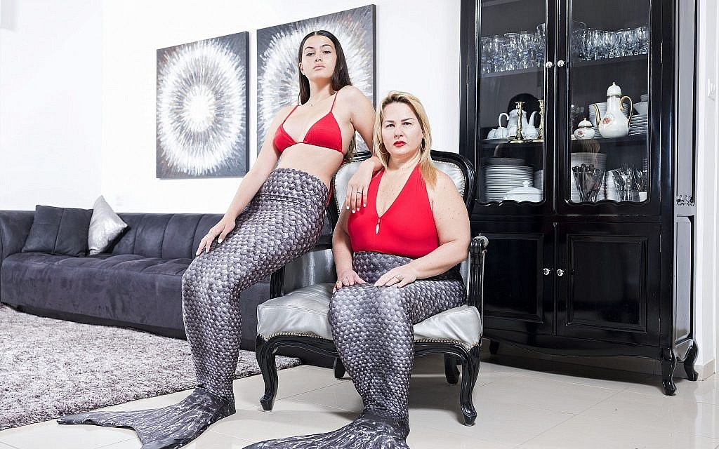In this Wednesday, March. 6, 2019 photo, Limor Kahlon, right, and her daughter Yam, members of the Israeli Mermaid Community, pose for a portrait as they wear mermaid tails at their home in Netanya, Israel. (AP Photo/Oded Balilty)