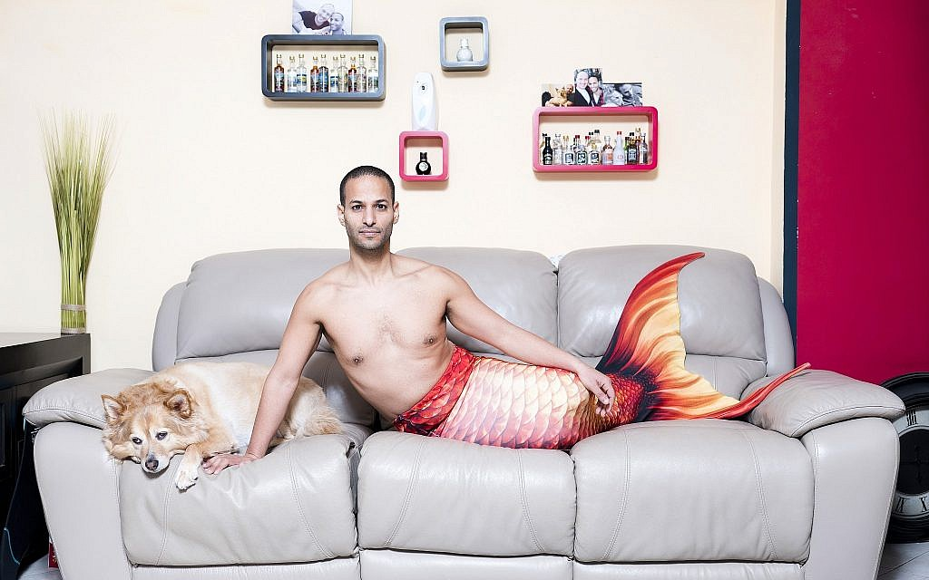 In this Friday, Feb . 22, 2019 photo, Udi Frige, a member of the Israeli Mermaid Community, poses for a portrait as he wears a mermaid tail at his home in Yahud, Israel. (AP Photo/Oded Balilty)