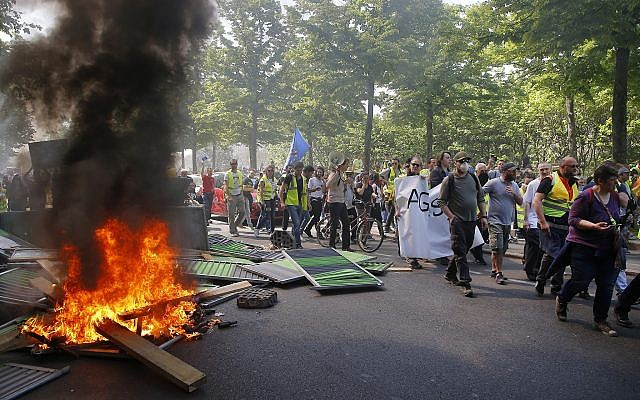 Protestors march by a burning pile of wood during a yellow vest demonstration in Paris, Saturday, April 20, 2019. (AP/Michel Euler)