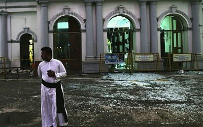 A Sri Lankan catholic priest stands near broken glass in front St. Anthony's Church in Colombo, Sri Lanka, Friday, April 26, 2019. Priests have allowed journalists inside St. Anthony's Church in Sri Lanka for the first time since it was targeted in a series of Islamic State-claimed suicide bombings that killed over 250 people.  (AP Photo/Manish Swarup)